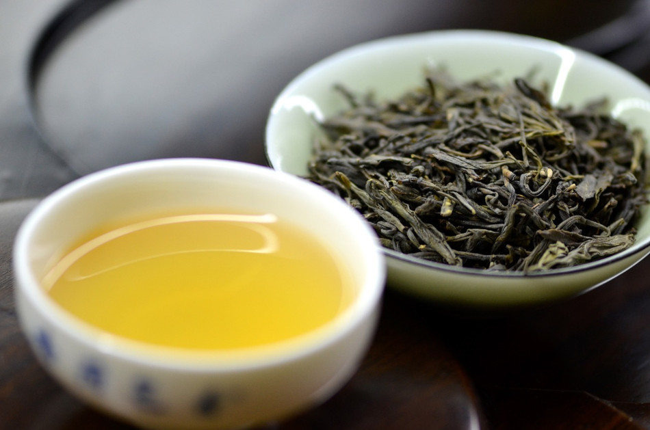 A cup of green tea sits next to a dish filled with green tea leaves.