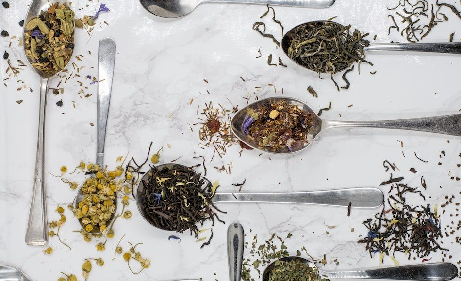 dried tea leaves of different varieties on silver spoons that lay on a white tablecloth on table around 6 spoons