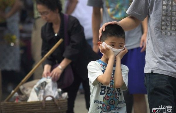 Boy covers face from smoke at Qingming festival.