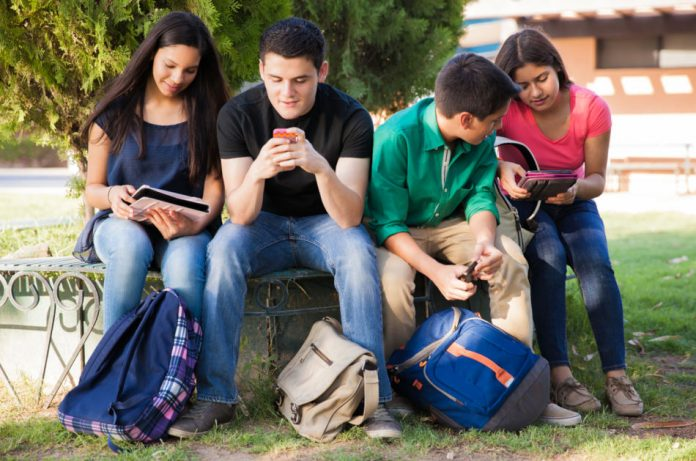 Boys and girls sit outside with school bags using mobile devices and tablets.