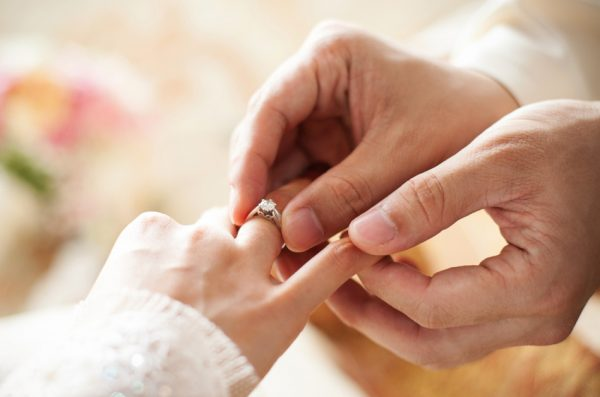 A man places a wedding ring on his bride's finger.