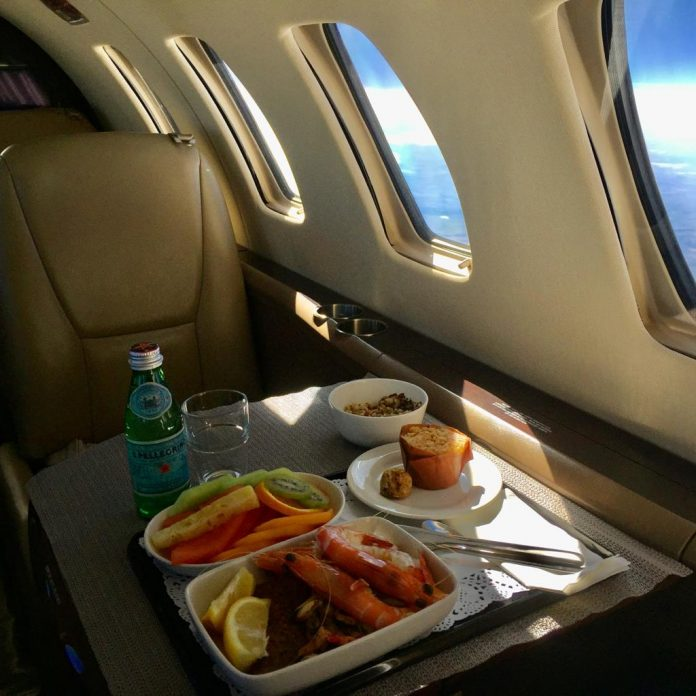 Meal on a private jet consisting of large prawns with lemon wedges, a bowl of melon, kiwi fruit and pineapple, a muffin, and a small bottle of mineral water.