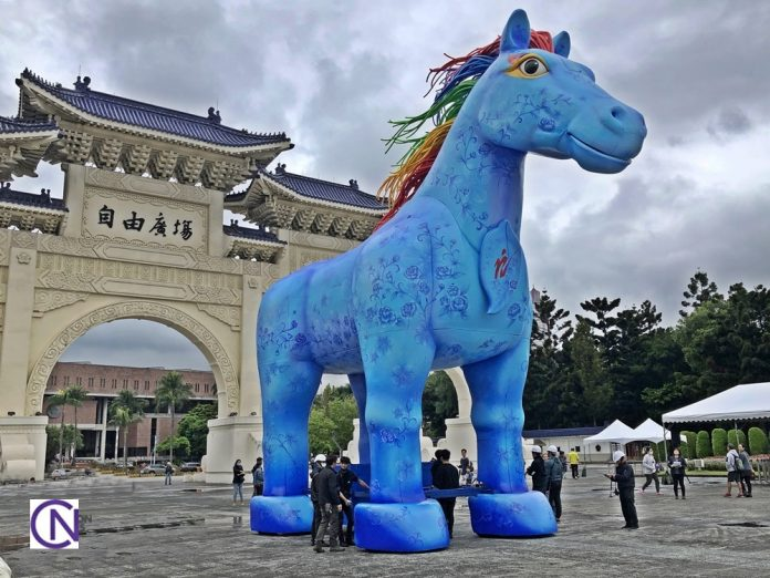The giant art installation of the Rain Horse is moved from the archway to the center of the plaza for the performance.