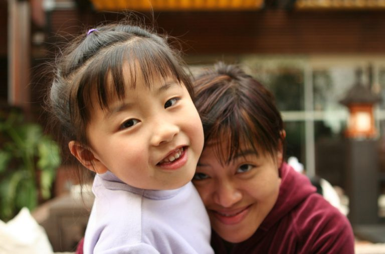 Asian child with her mother, smiling for the camera.
