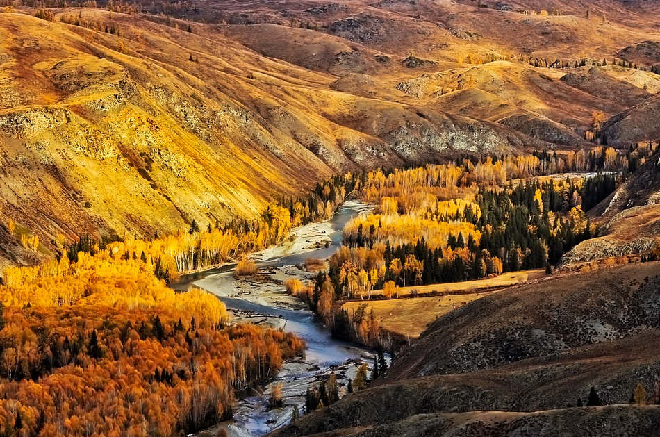 A river at the foot of some mountains with trees seen along the banks during fall.