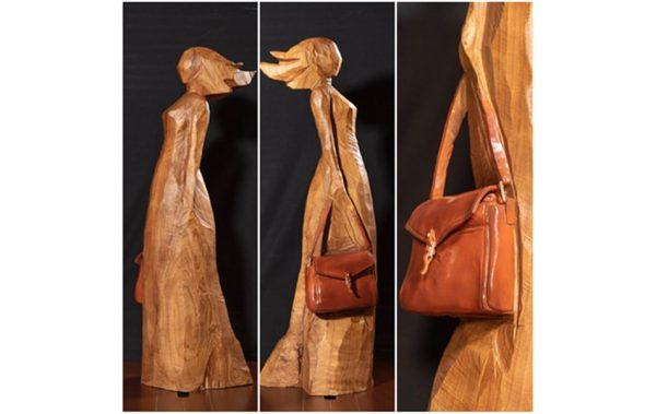 A woman carrying a purse, sculpted out of wood, by Cai Mingfeng.