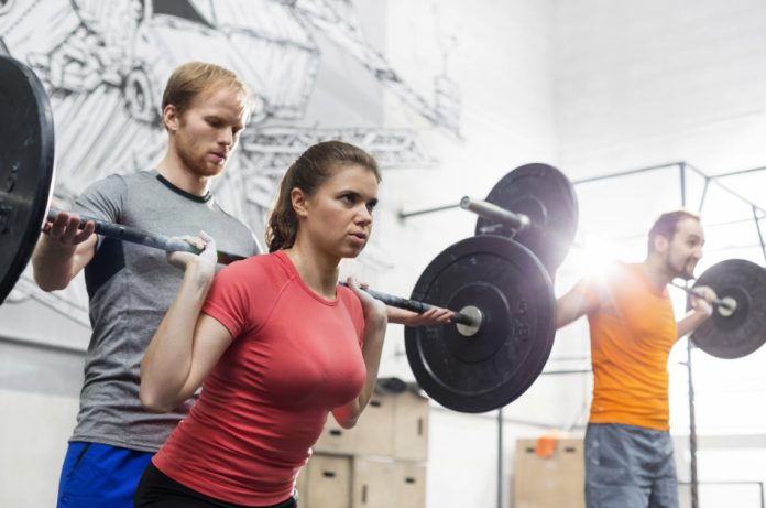 Coach at the gym helps a woman have proper form while lifting free weights.