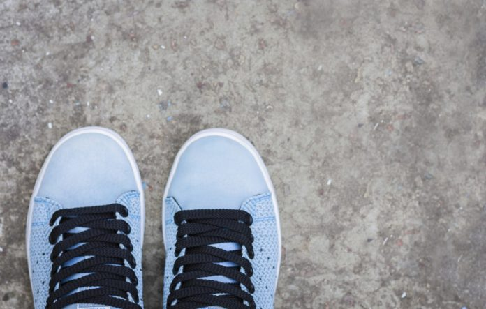 Sneakers of blue suede with black laces on the sidewalk.
