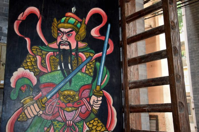 Colorful painting of door god on the traditional sliding wooden poles door in Guangzhou in China.