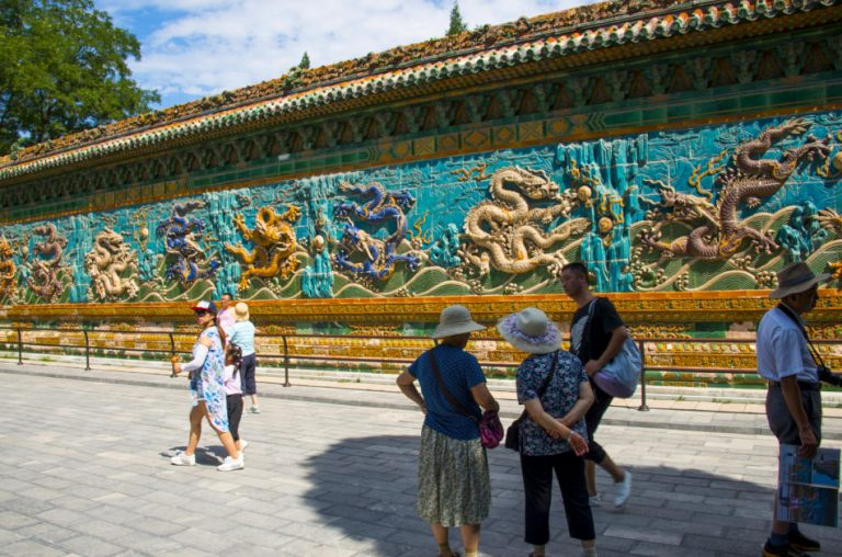 People standing in front of the Nine-Dragon Wall in the Forbidden City, Beijing, China.