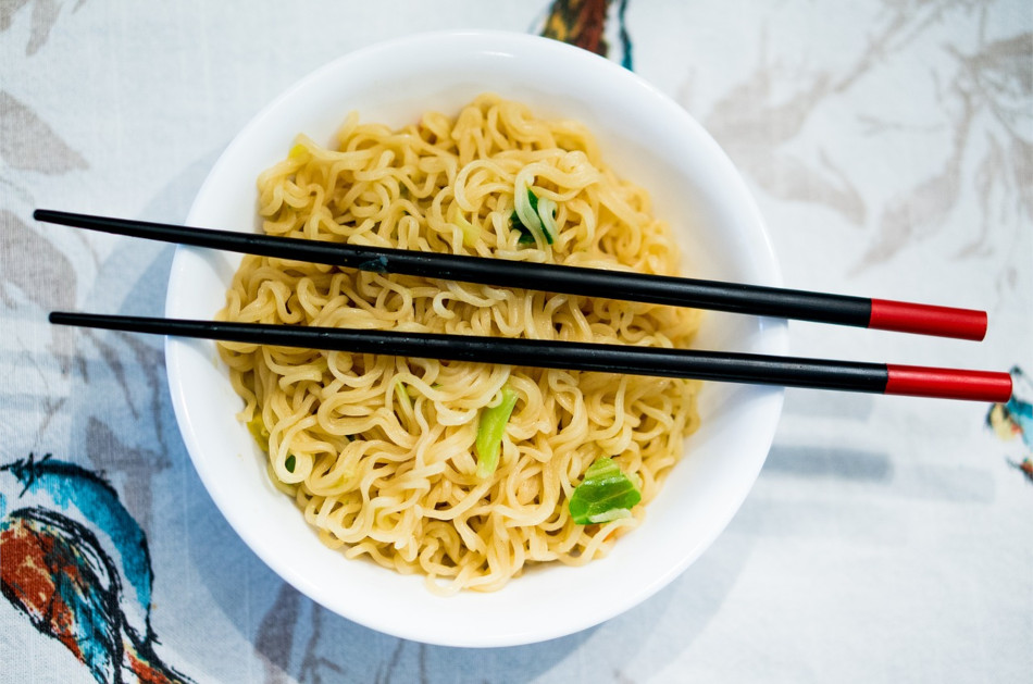 Ramen noodles in a white porcelain bowl with black lacquered chopsticks that have red tips balanced on top.