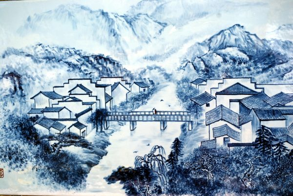 detail of porcelain depicting chinese village with houses bridge mountain and river