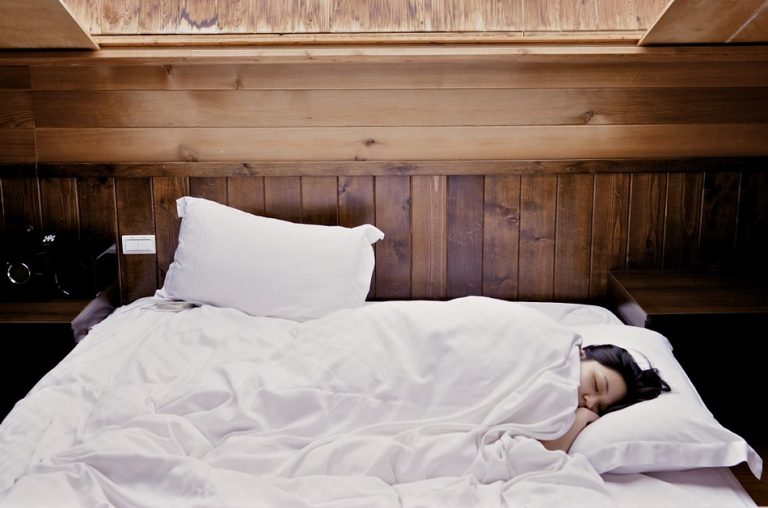 An Asian woman sleeps on a bed under a white comforter in a room with dark wood paneling.