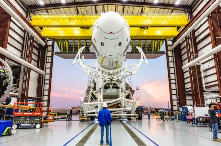 SpaceX Dragon rocket and capsule being rolled out of a storage hangar.
