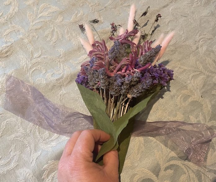 ribbon being tied to bouquet of dry flowers