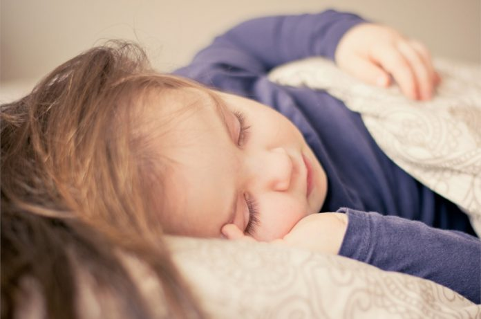 Toddler wearing a blue top asleep on a pillow, covered by a blanket.