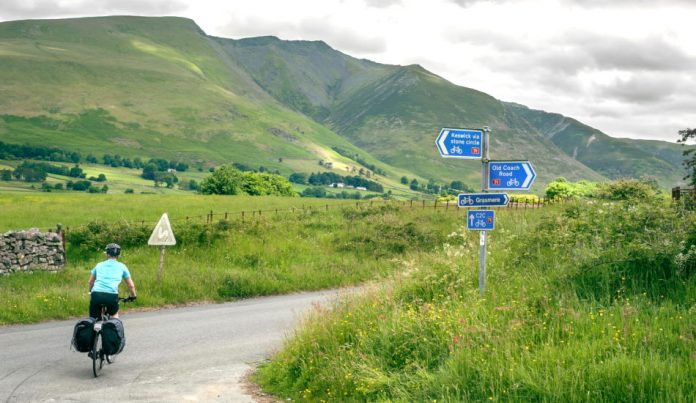 Lone cyclist riding the Coast to Coast C2C cycle route through the hills of the Lake District, Cumbria, UK.