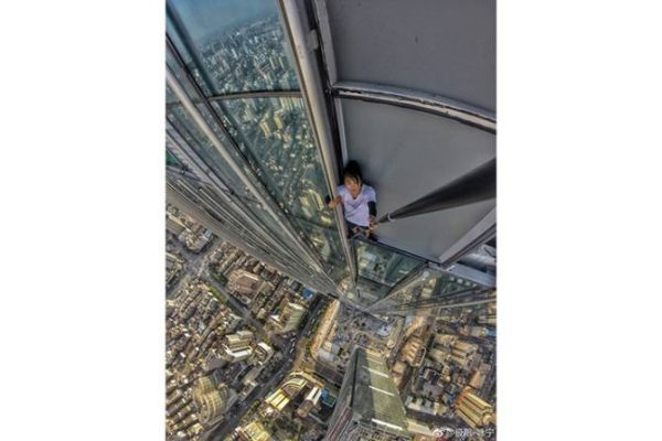 chinese man with selfie stick wedged between tall skyscraper building
