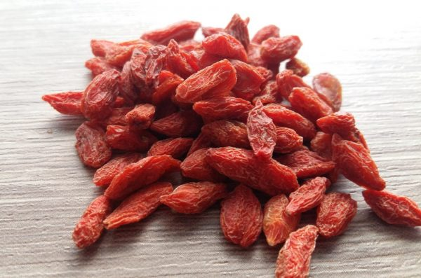 A pile of dried Goji berries sits on a wooden surface.