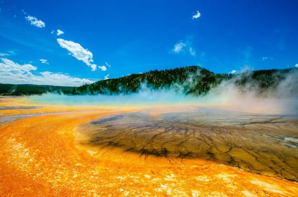 Grand Prismatic Spring with it's bright orange soil, clouds hovering and green mountain in the background, Yellowstone National Park