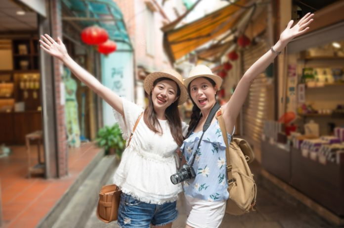 Two smiling Asian girls wearing hats pose for a picture in front of some shops while touring a mountain town in Taiwan.