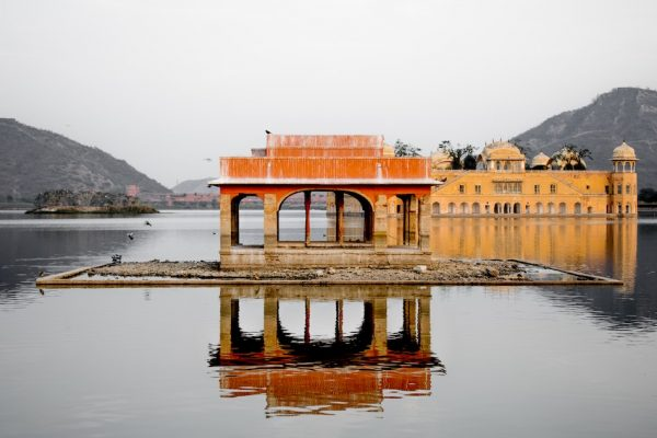 orange water palace in India reflecting off water on an overcast day