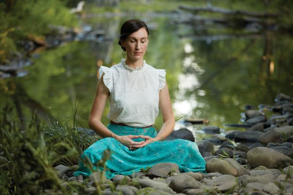 singer songwriter katy mantyk meditates Falun Dafa by a river she is sitting with legs folded and hands conjoined