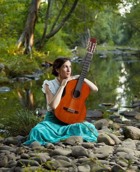 singer songwriter katy mantyk has released new song michelangelo and she holds guitar and sits by river