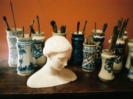 sculpture of ladies head in art studio surrounded by paint brushes
