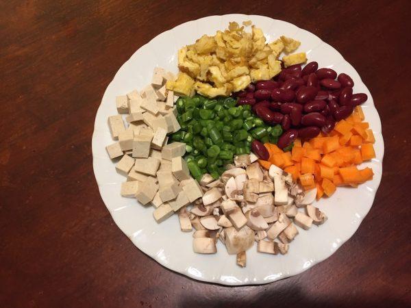 tofu, mushroom, carrot, beans, egg, kidney beans chopped on a plate