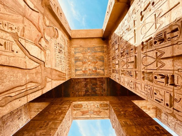 The Theban Necropolis in Egypt large stone orange sandstone structures with Egyptian painting and writing carved on the ceiling and walls