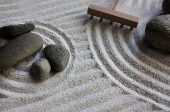A rake being passed through the sand of a Zen garden makes a circle around some rocks.