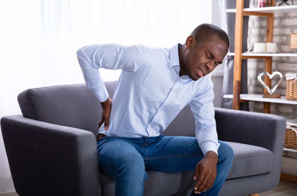 African American man holding his lower back in pain while sitting on a gray sofa.