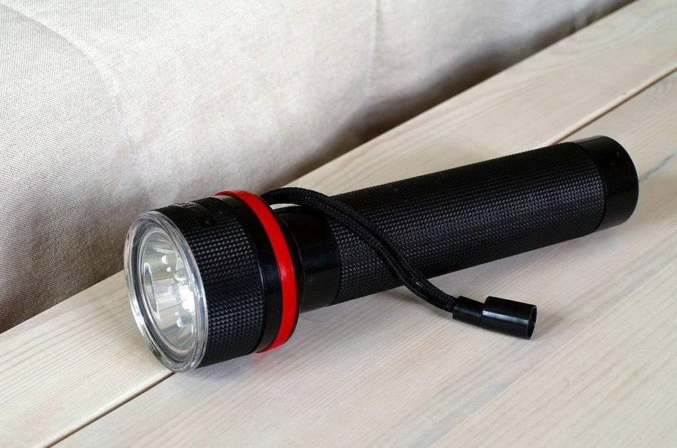 A black flashlight sits on a nightstand.
