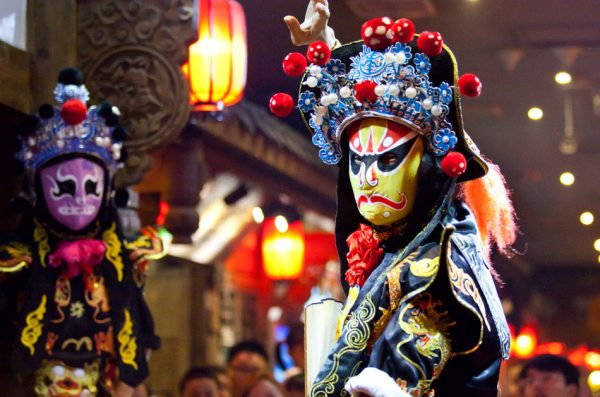 Traditional Chinese opera performance in Sichuan Province, China, with one performer wearing a yellow mask and the other performer wearing a purple one.