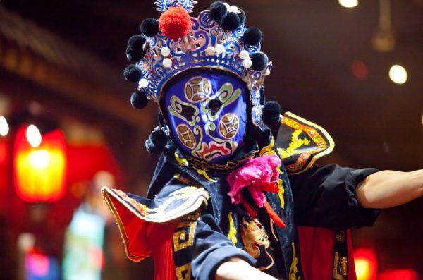 Traditional Chinese opera performance in Sichuan Province, China, with a performer wearing a blue mask.