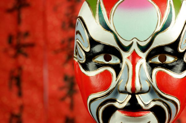 Red Chinese opera mask in front of a red background that has Chinese characters written on it in black ink.