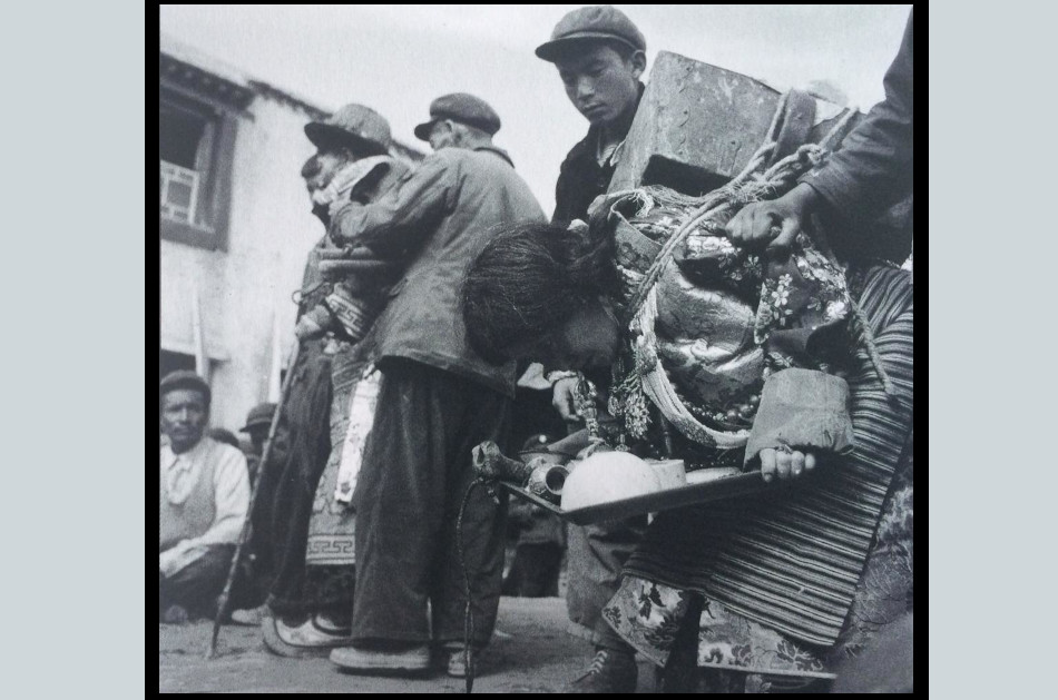 A Tibetan man and his wife being tortured and humiliated in a public struggle session during the Cultural Revolution in China.