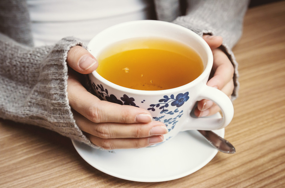 Female hands holding a blue and white porcelain cup filled with tea.