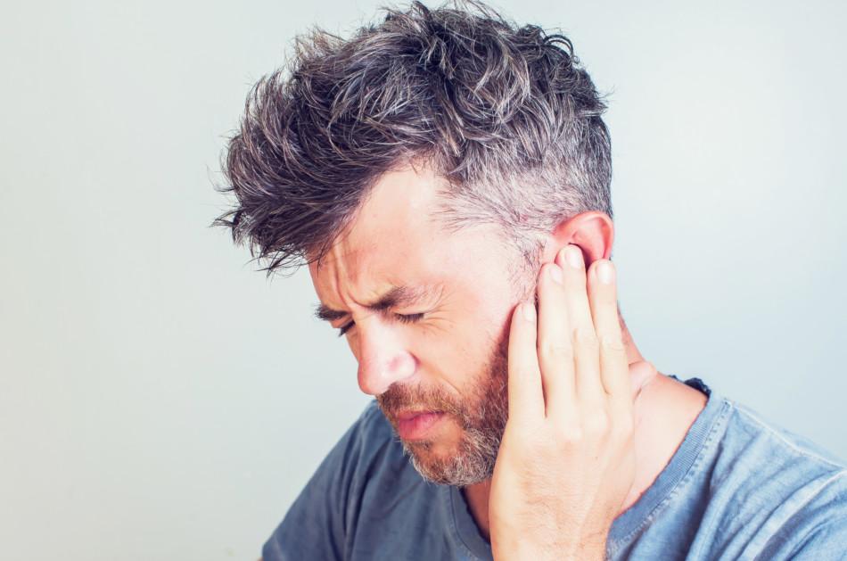 Man with an earache holding his left ear.