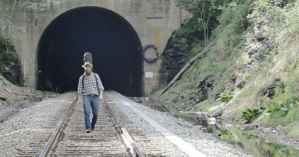 man walks down train track with guitar on back