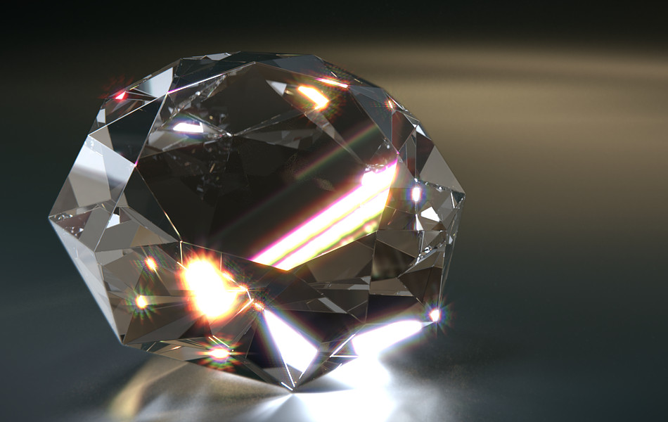 A diamond sits on a dark surface with light refracting off it.