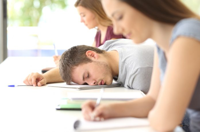 Tired male student sleeping in class between two other female classmates who are busy taking notes.