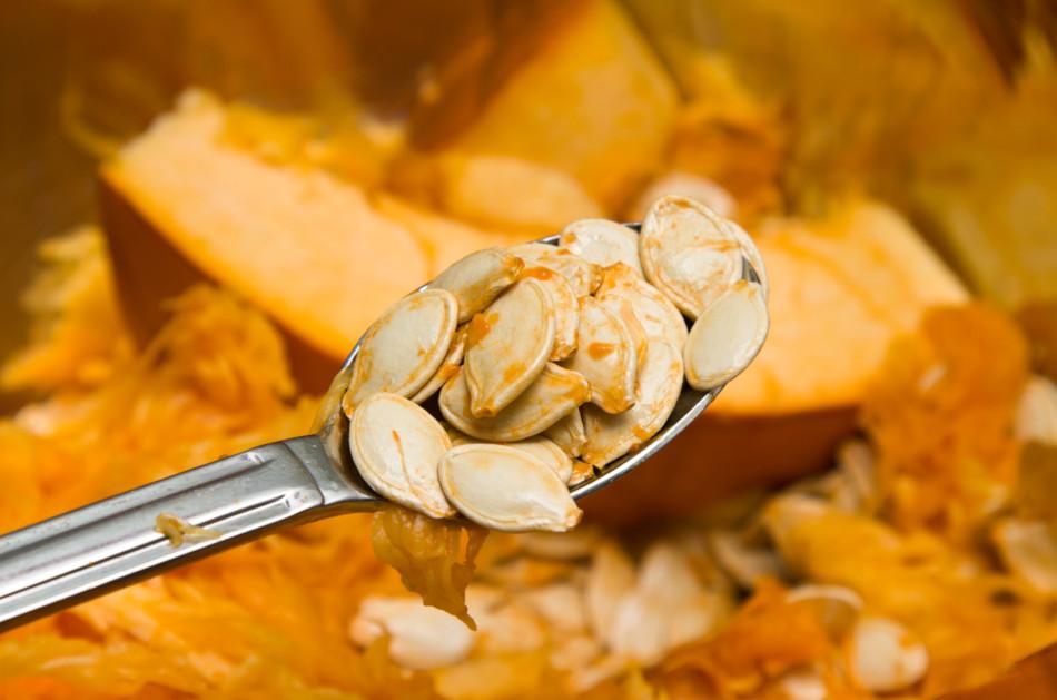 Pumpkin seeds on a spoon after carving a pumpkin.