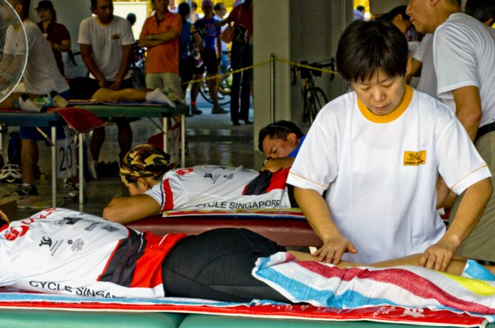 Cyclists receive a Tiger Balm massage on their legs after a race.