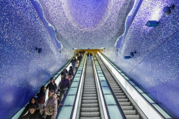 purple roof and walls of Toledo station Naples Italy people are on the escalators
