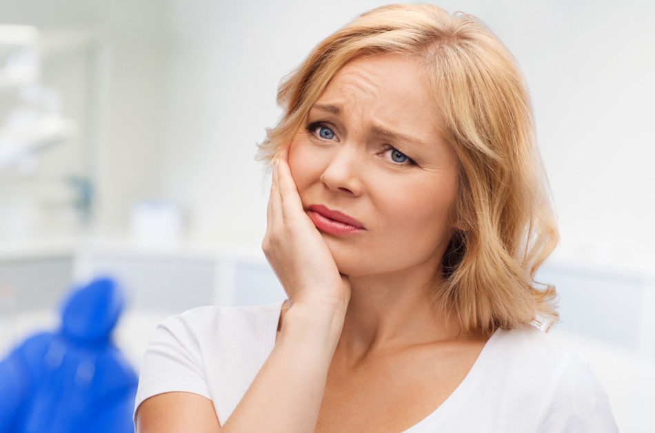 Blonde woman holding the right side of her face as though she has a toothache.
