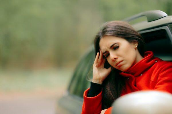 Woman in a red jacket standing by a car and rubbing her temple with a pained expression.
