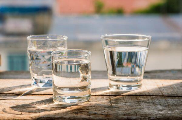 Three clear drinking glasses filled with water sit on a wooden surface outdoors.
