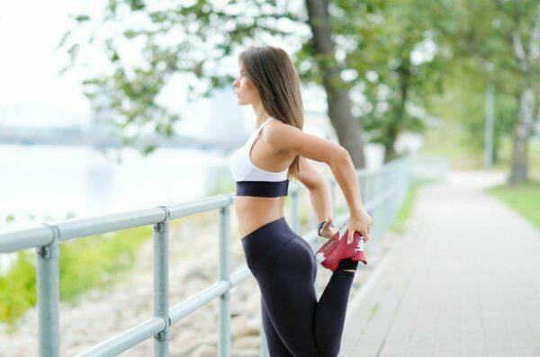 Young, healthy woman stretches in preparation to jog through the park.